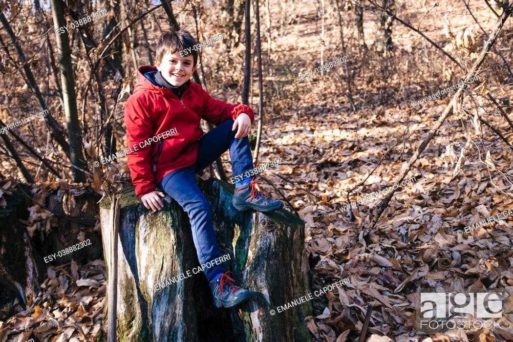 Stock Photo: portrait of child in the forest on the background of trees in winter and autumn season.