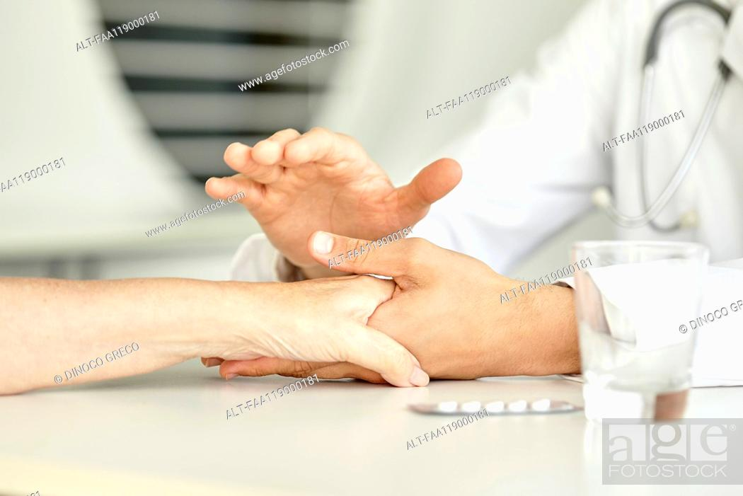 Stock Photo: Close-up of doctor holding patient's hand.