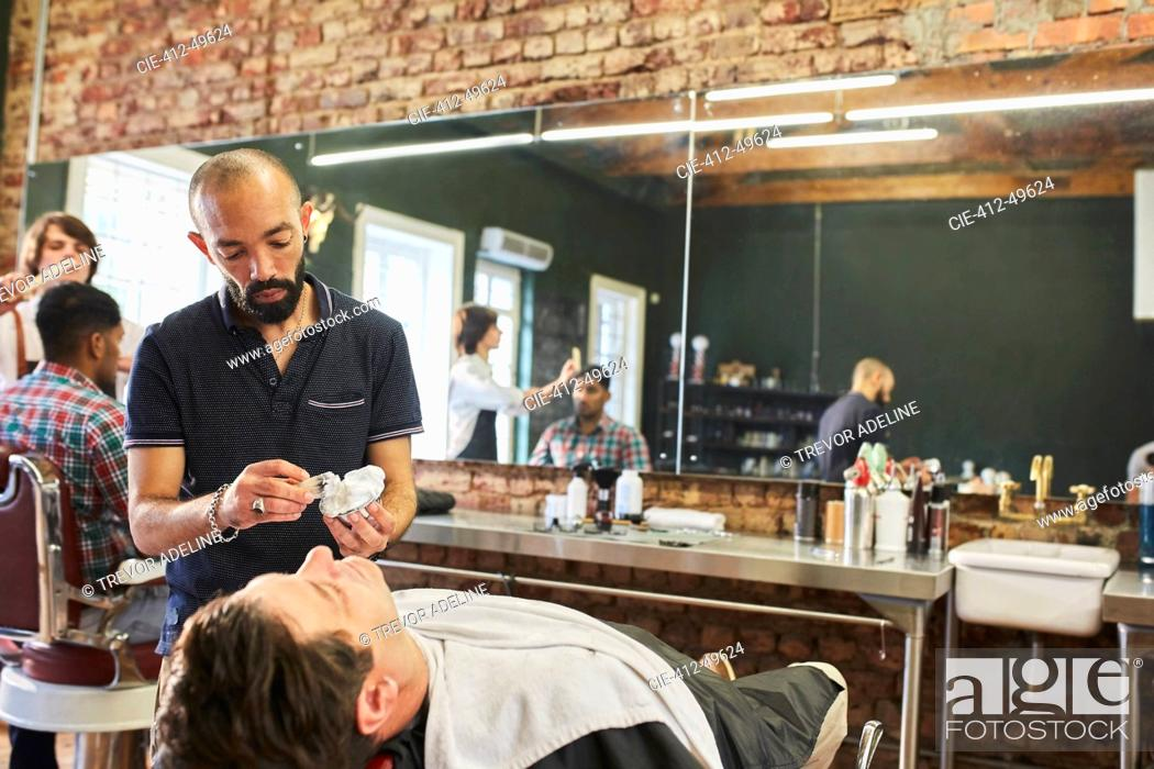 Stock Photo: Male barber preparing to shave face of customer in barbershop.