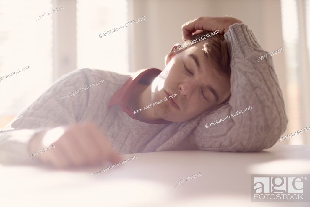 Stock Photo: Young tired man lying on table with closed eyes, indoors.
