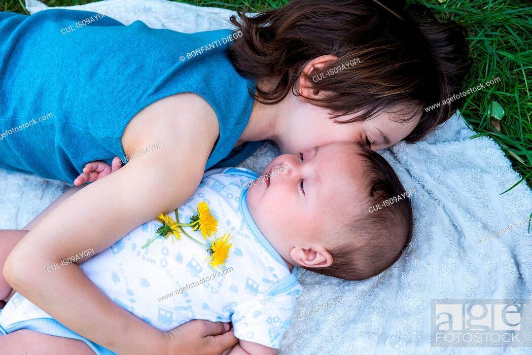 Stock Photo: Boy hugging baby brother in garden.