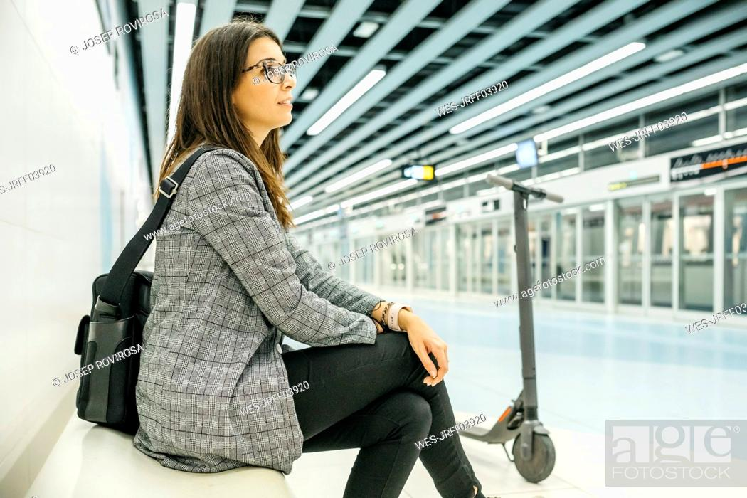 Stock Photo: Young businesswoman with e-scooter waiting at the subway station.