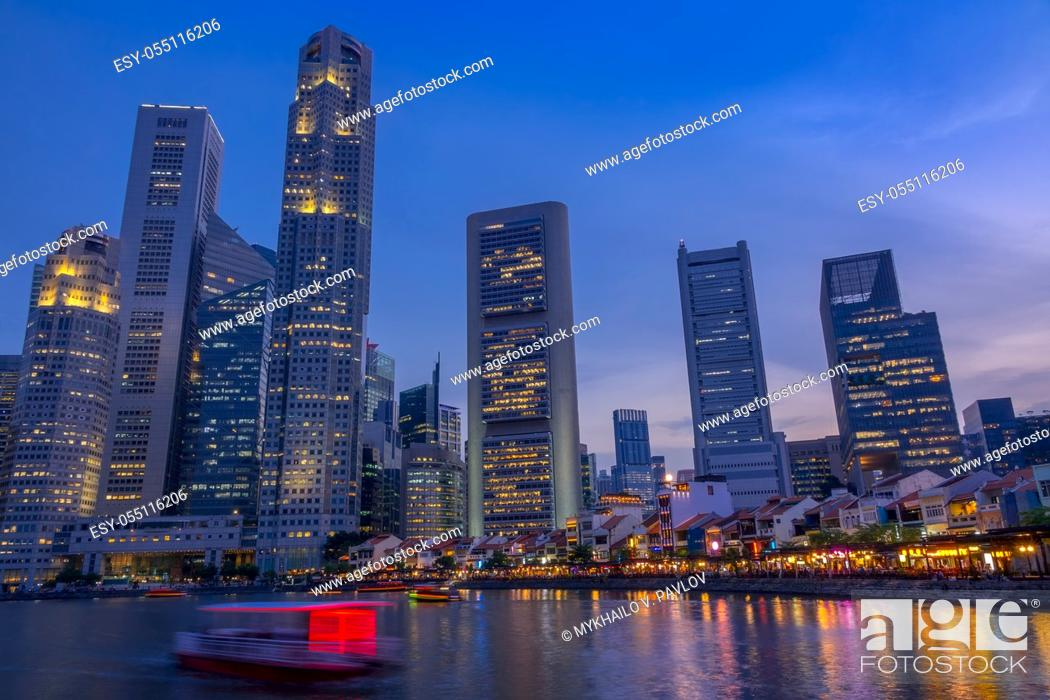 Stock Photo: Singapore. Quay with cafes and skyscrapers. Pleasure boats. Dusk.