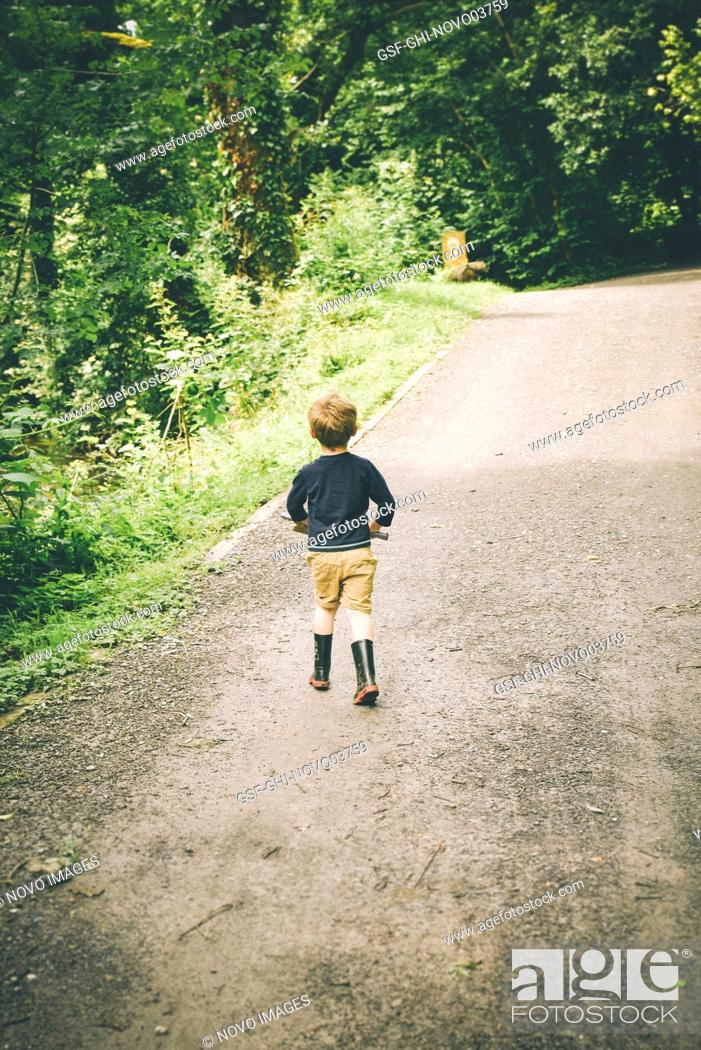 Imagen: Rear View of Young Boy walking down Rural Road in Shorts and Rubber Boots.