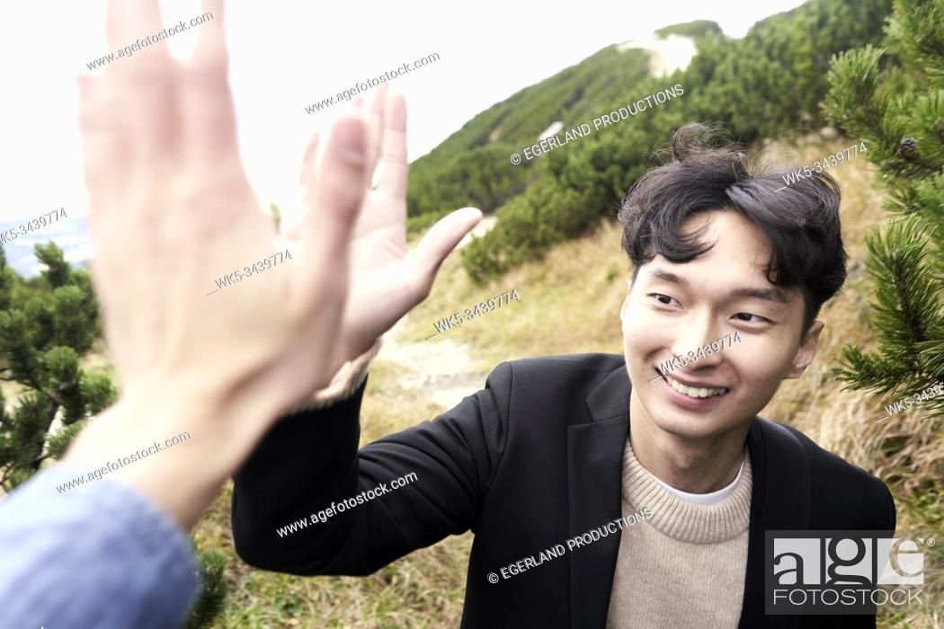 Imagen: Korean man giving high five to friend while hiking at mount Untersberg near Salzburg, Austria, Europe.