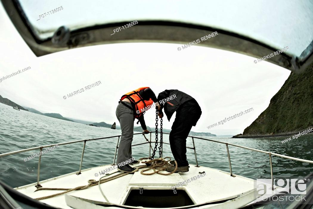 Stock Photo: Two people engaged in lowering an anchor off the bow of a boat, Avacha Bay, Russia.