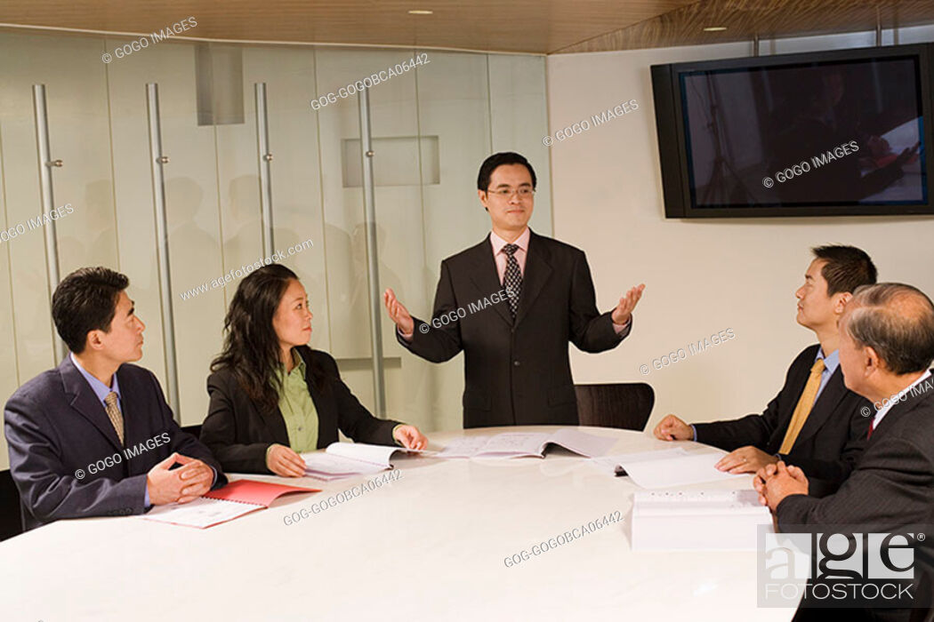 Stock Photo: Businessman standing up in a meeting.