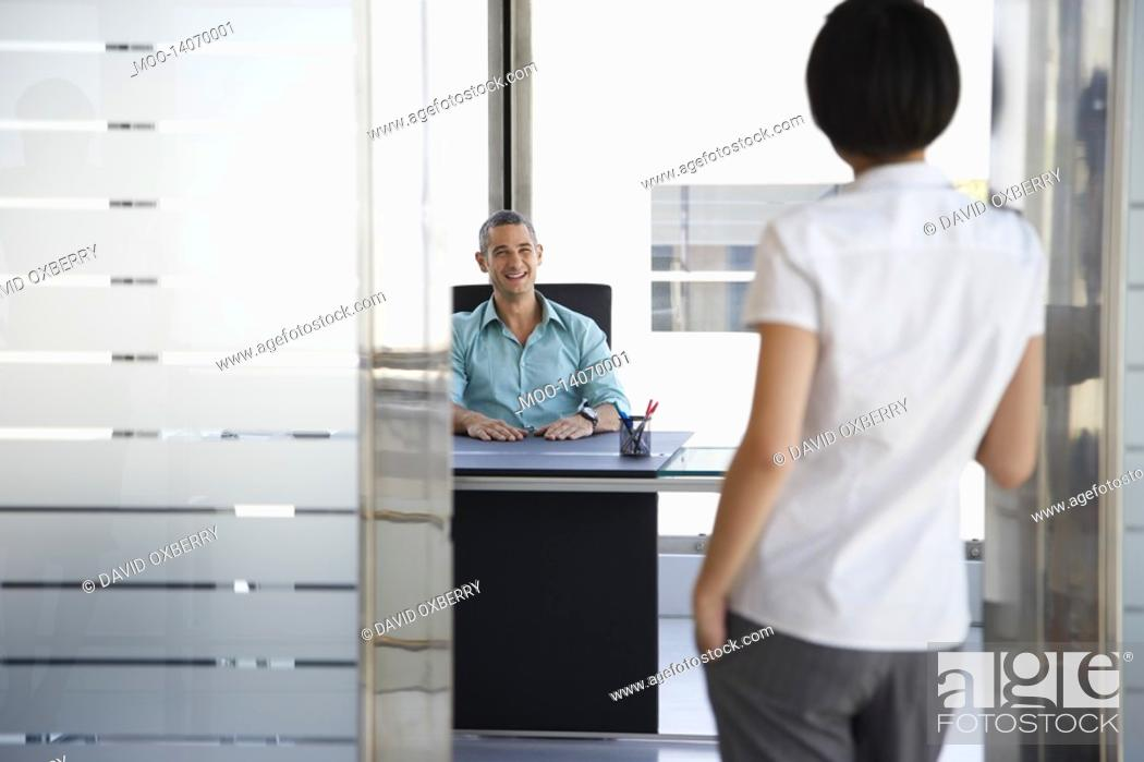 Stock Photo: Man talking to woman standing in doorway of his office.