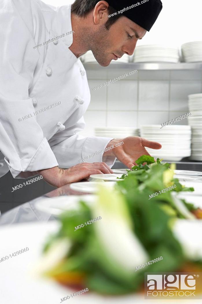 Stock Photo: Male chef preparing salad in kitchen.