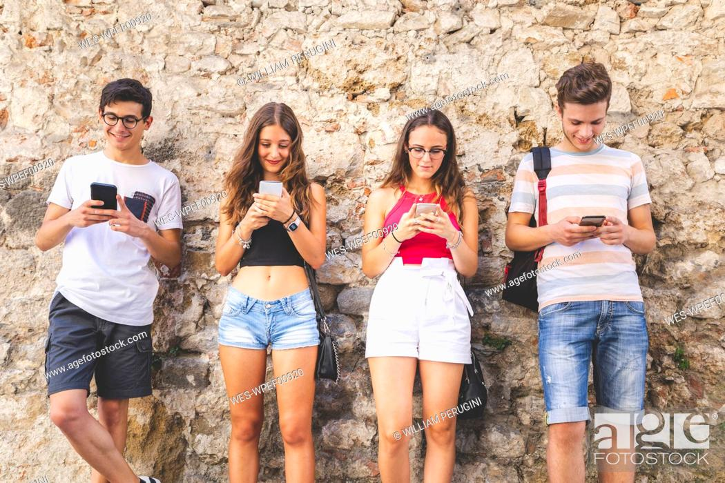 Stock Photo: Group of friends standing at a wall using their cell phones.