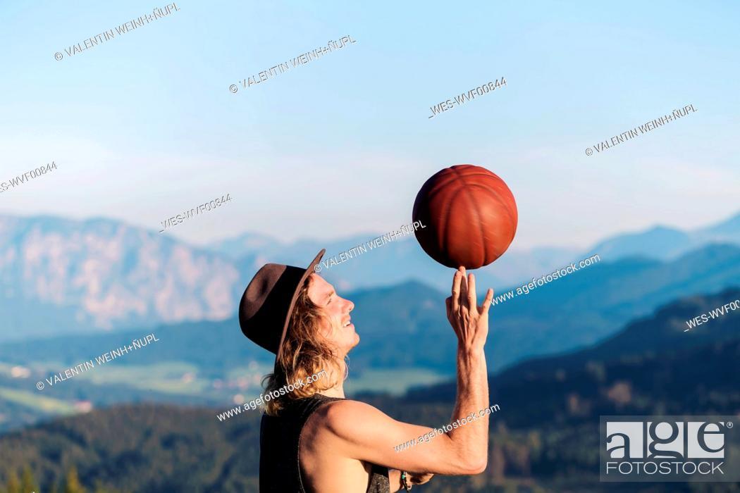 Photo de stock: Austria, Mondsee, Mondseeberg, young man balancing basketball on his finger.