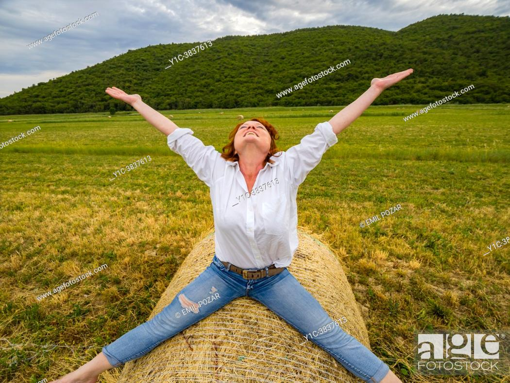 Imagen: Joy of life mature woman spreading wide on countryside haystack looking up joy of life.