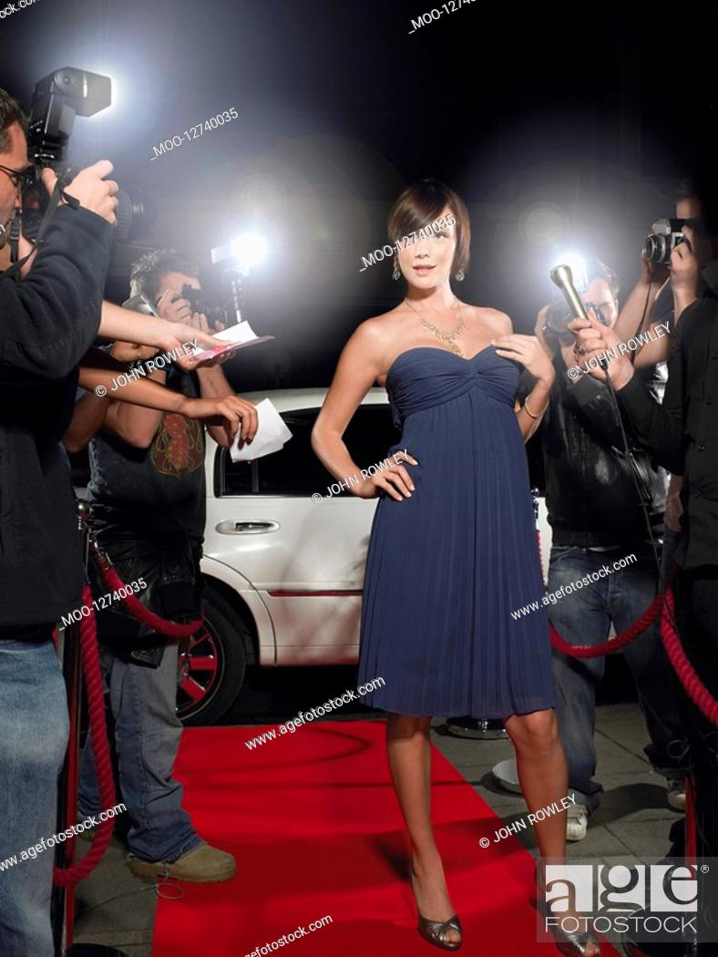 Stock Photo: Woman posing on red carpet being photographed by paparazzi.