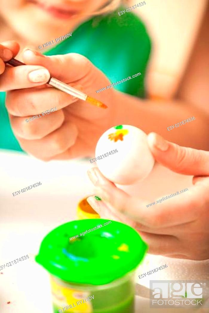 Stock Photo: Woman and girl drawing flowers on easter eggs.