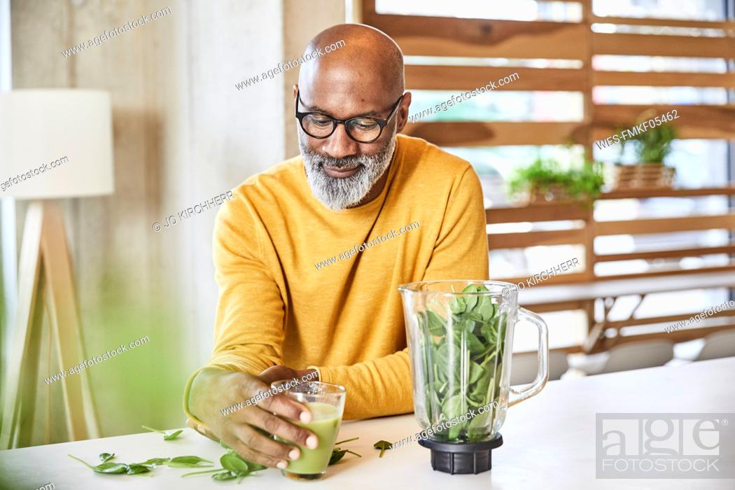 Stock Photo: Mature businessman in office preparing a smoothie.
