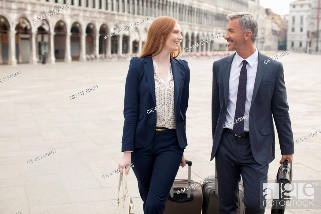 Stock Photo: Smiling businessman and businesswoman pulling suitcases through St. Mark's Square in Venice.