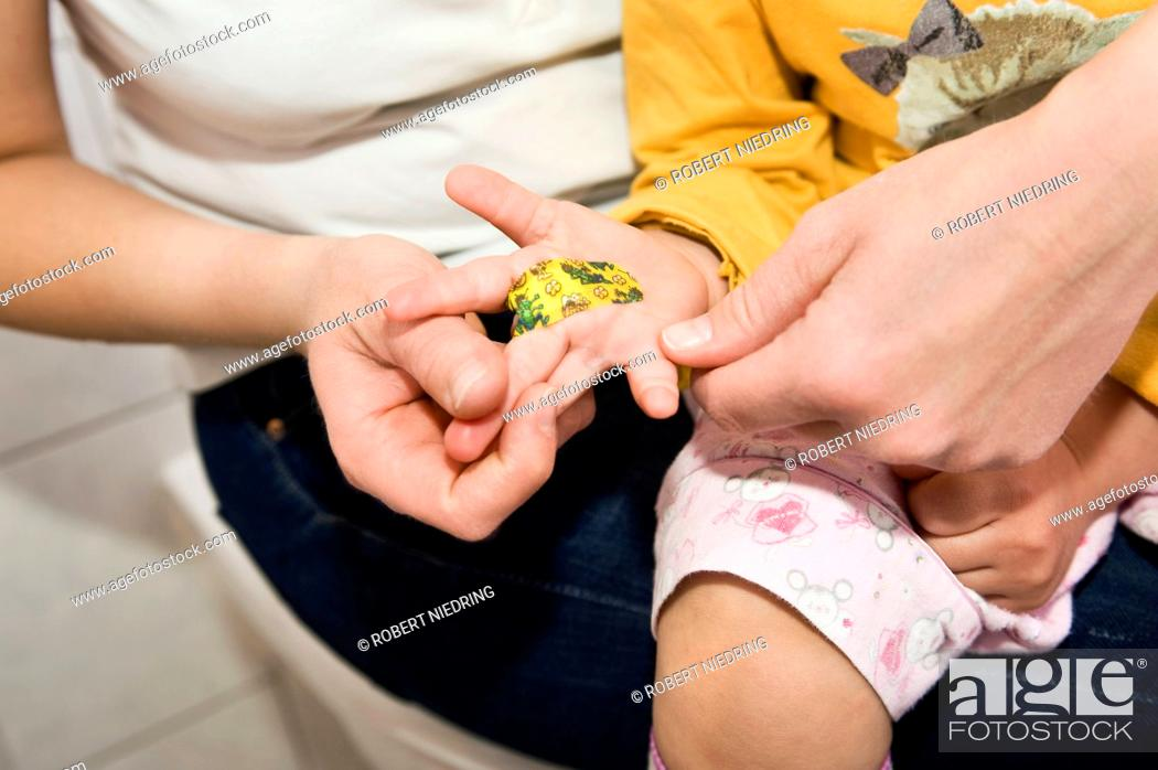 Stock Photo: Daughter showing bandage sitting on mother lap in bathroom, close up.