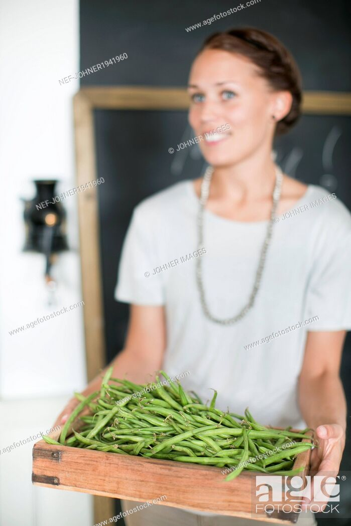 Stock Photo: Woman holding green beans in wooden box.