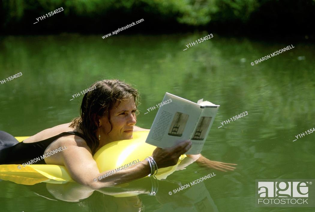 Stock Photo: Woman, 30-40 years old, reading book while floating in water on an inflatable raft. Midwest, USA.