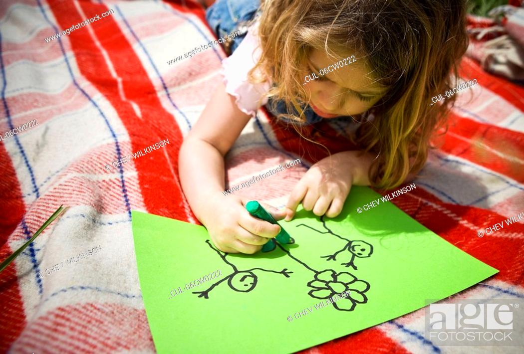 Stock Photo: Girl colouring a drawing.