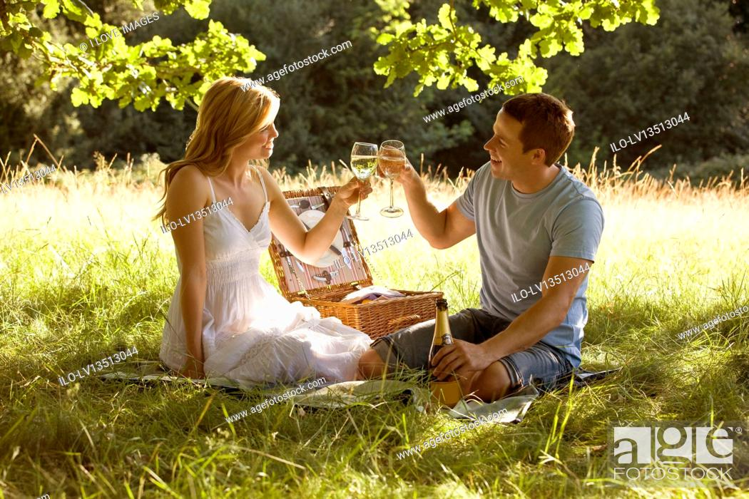 Stock Photo: A young couple having a picnic, making a toast.