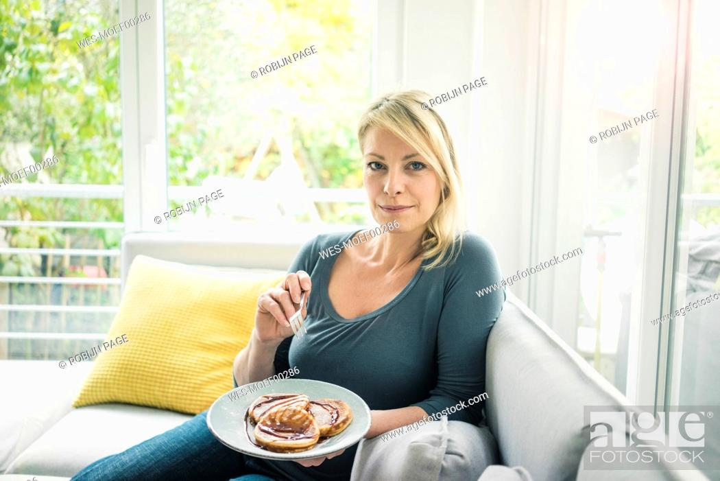 Stock Photo: Portrait of woman sitting on couch eating pancakes.
