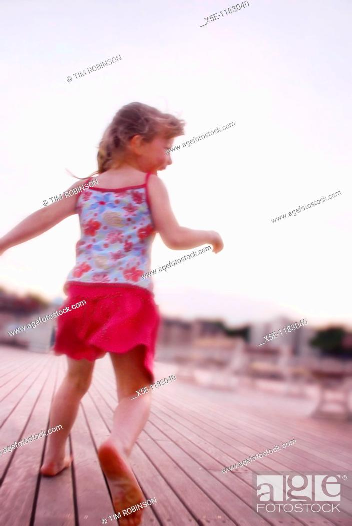 Stock Photo: Rearview 6 year girl running away on pier and laughing with joy.