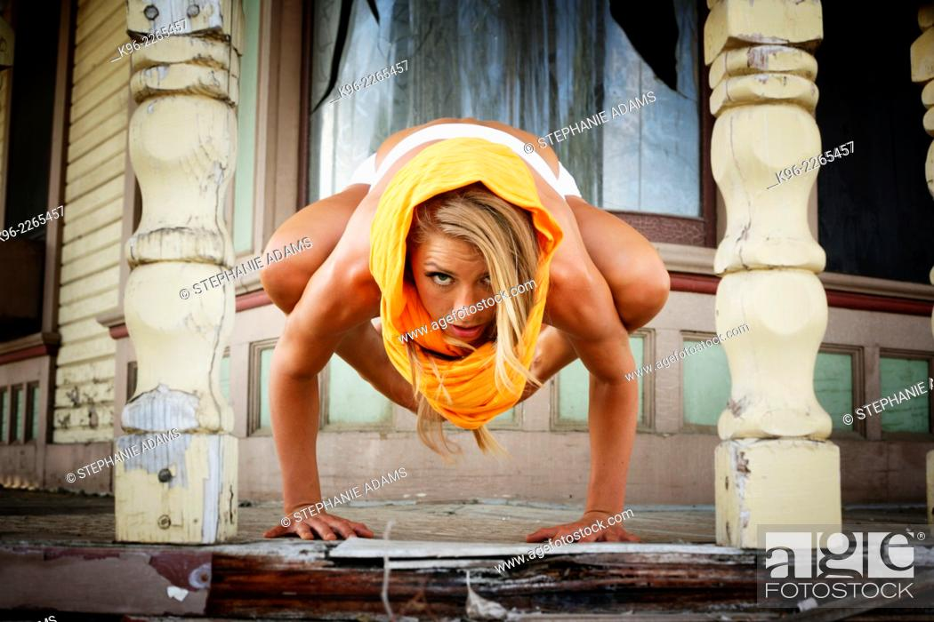 Photo de stock: Female on old porch of a house holding a difficult yoga pose.