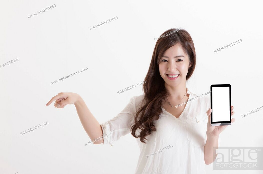 Imagen: Young business woman holding mobile phone and pointing with smile,.