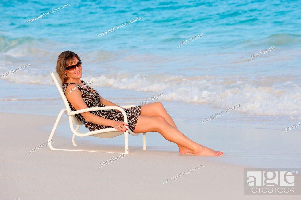 Stock Photo: Woman enjoys beach chair on the sand, Bermuda Island, Atlantic Ocean.