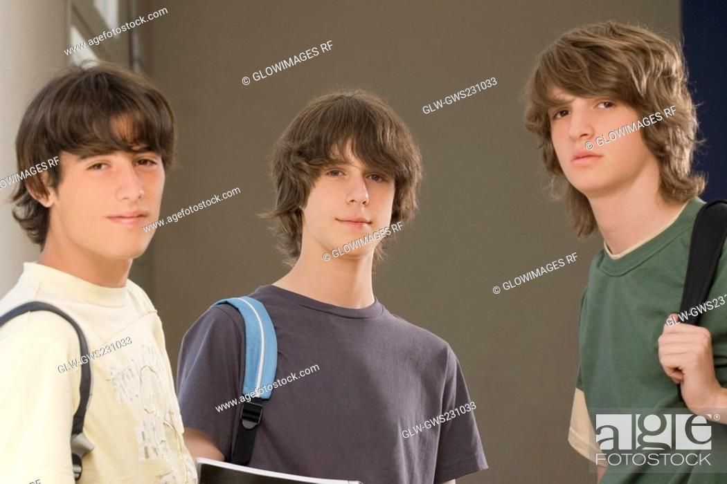 Stock Photo: Portrait of two teenage boys standing with a young man.