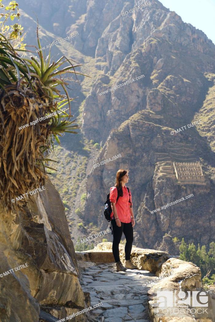 Stock Photo: Young female tourist gazing at Inca ruins, Ollantaytambo, Peru.