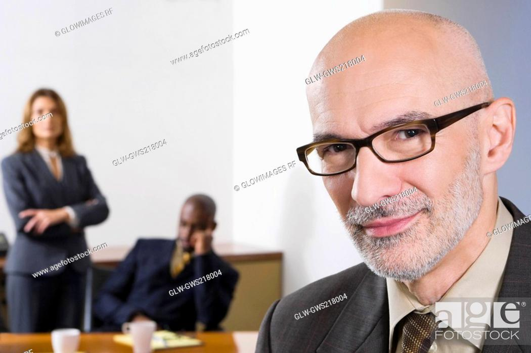 Stock Photo: Portrait of a businessman with his colleagues in the background.