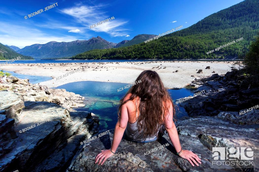 Imagen: A young woman looks out onto a sand bar from lower Myra Falls at the head of Buttle Lake in Strathcona Park. Vancouver Island, British Columbia, Canada.