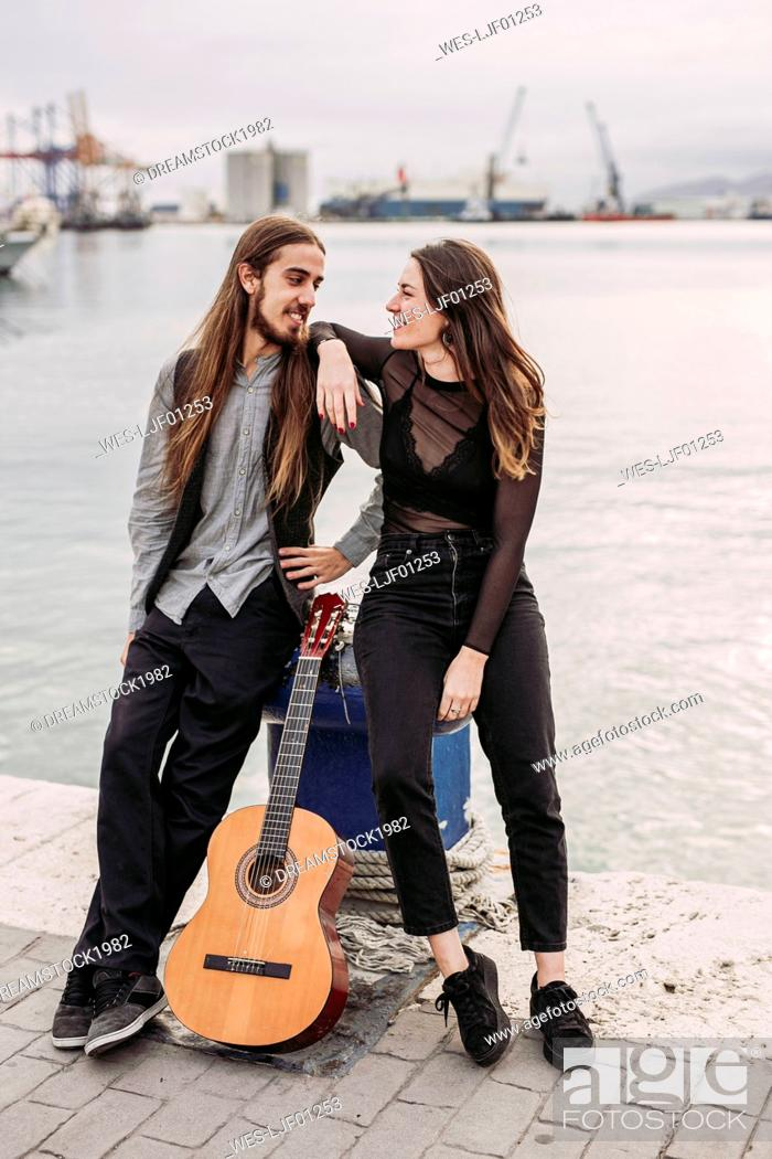 Imagen: Young couple with a guitar at the port.