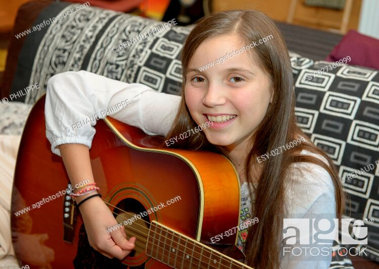Stock Photo: Young teen girl playing acoustic guitar on sofa.