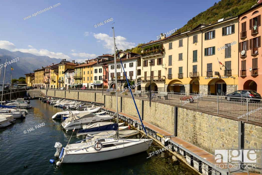 """Stock Photo: DOMASO, ITALY - OCTOBER 04: fall sun lightens harbor, old houses and little traffic on ancient """"""""Regina"""""""" road crossing historical touristic village on Lario."""
