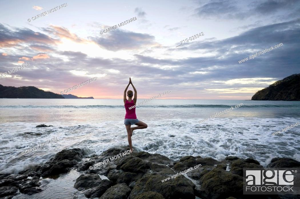 Stock Photo: Young woman doing yoga on rocks at sunset in front of ocean surf at Playas del Coco, Costa Rica.