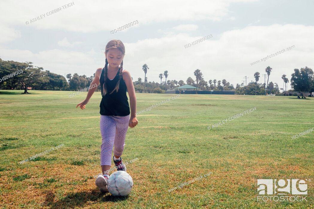 Stock Photo: Schoolgirl kicking soccer ball on school sports field.
