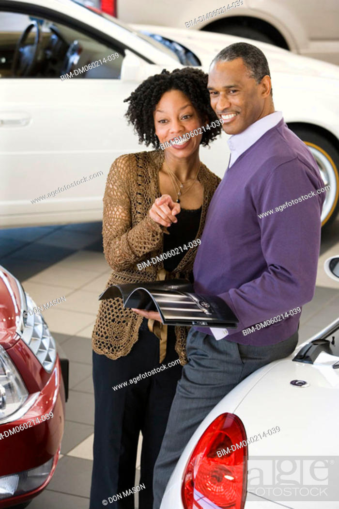 Stock Photo: Couple picking out a car to buy.