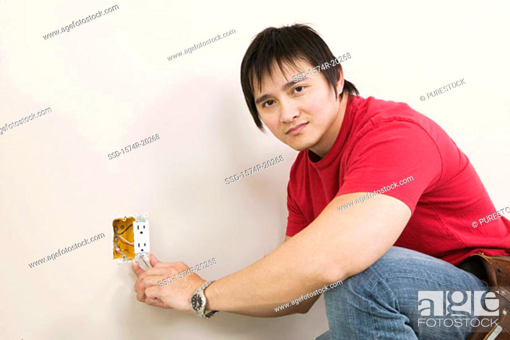 Stock Photo: Side profile of a young man holding a screw driver and repairing a power outlet.