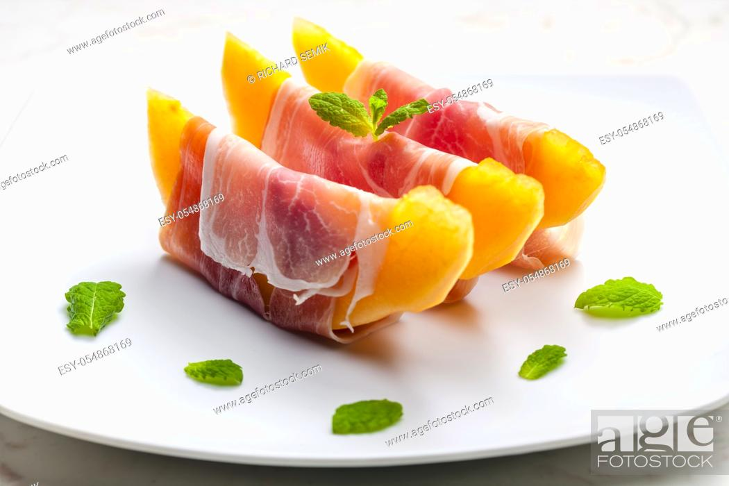Stock Photo: melon cantaloupe with smoked ham and mint.