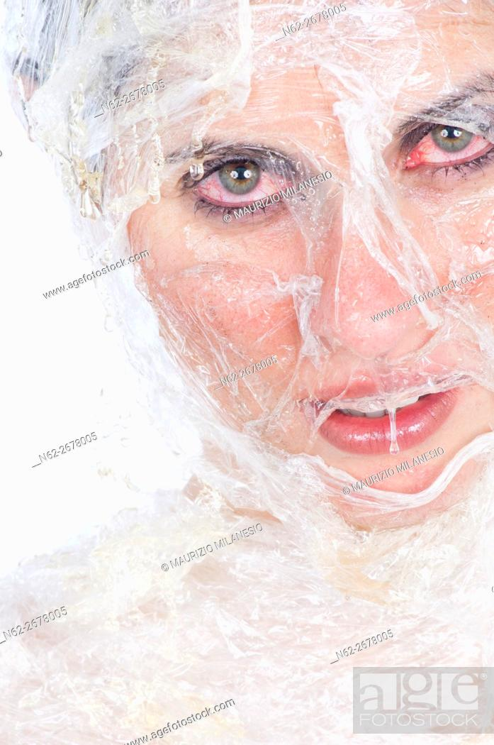 Stock Photo: Face of a girl wrapped in plastic wrap, she is doing a beauty treatment with honey, her eyes are red with irritation.