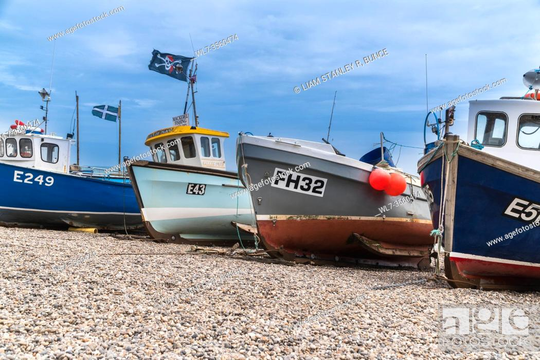 Stock Photo: Fishing boats moored up on shingle beach at Beer south Devon UK. June 2019.