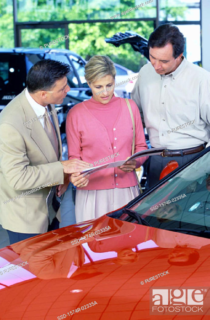 Stock Photo: Mid adult couple looking at a brochure in a car showroom.