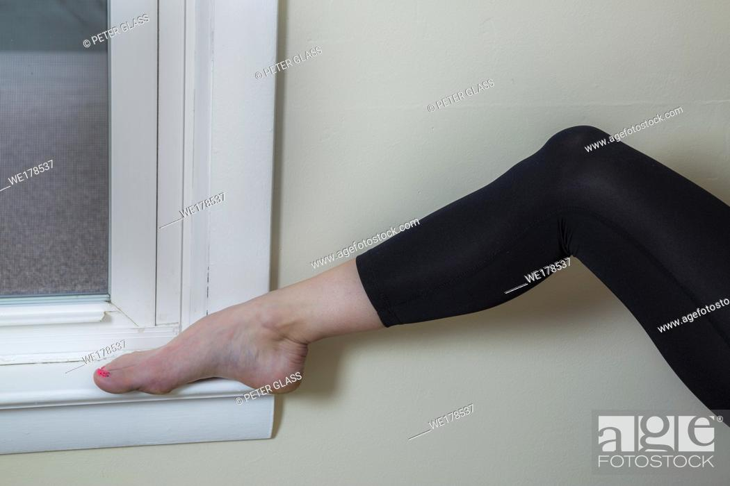 Stock Photo: Close-up of a young woman's foot on a window sill.