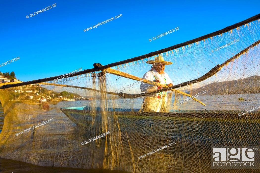 Stock Photo: Fisherman with butterfly fishing net in a lake, Janitzio Island, Lake Patzcuaro, Patzcuaro, Michoacan State, Mexico.
