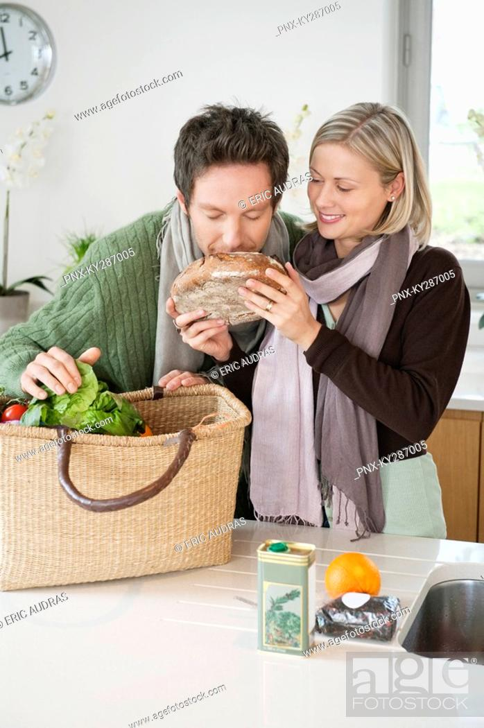 Stock Photo: Man smelling a loaf of bread with his wife standing beside him.