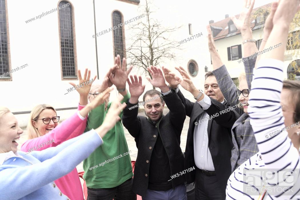 Stock Photo: Group of friends raising hands together. Starnberg, Bavaria, Germany.