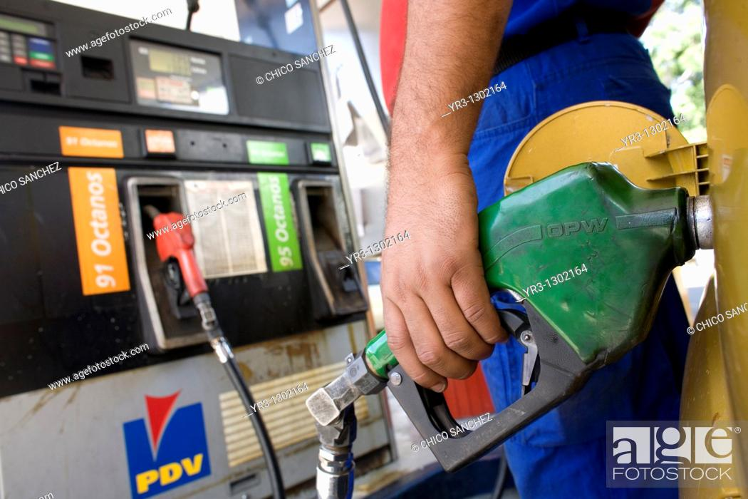 Stock Photo: A workers pumps gas at a gas station in Caracas, Venezuela, July 23, 2008.